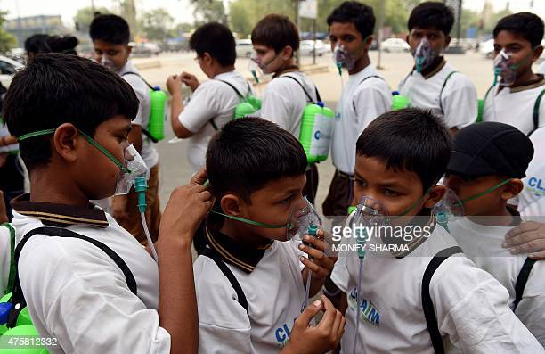 An Indian schoolchild adjust the mask of another before the start of an event to spread awareness of the problem of air pollution in New Delhi on...