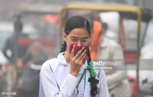 An Indian schoolgirl covers her face with a handkerchief amid heavy smog in the old quarters of New Delhi on November 8 2017 Delhi shut all primary...