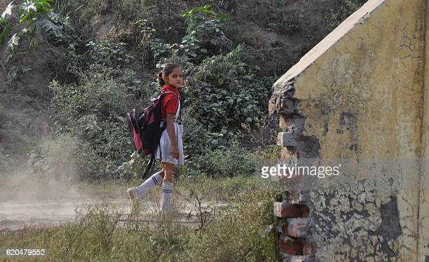 An Indian schoolgirl walks home after her school was closed in areas around the IndiaPakistan border in Jammu on November 2 2016 Hundreds of schools...