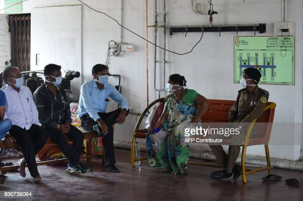 An Indian security guard and relatives of a Swine flu patient interact outside the isolation ward of the Ahmedabad Civil Hospital in Ahmedabad on...