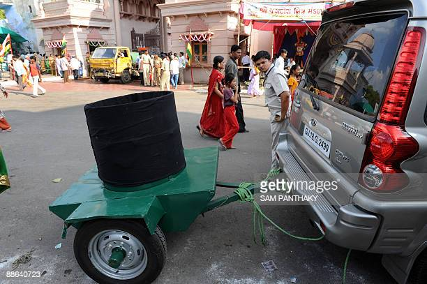 An Indian security guard keeps vigil as a Bomb Removal Basket attached to a special vehicle is kept ready prior to the visit by Gujarat state Chief...