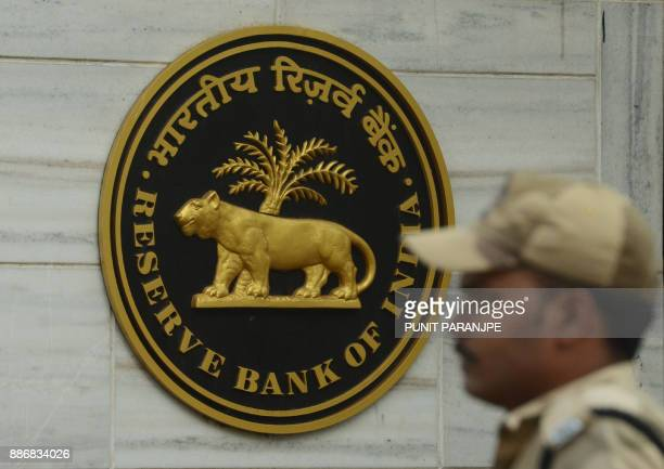 An Indian security guard stands at the entrance of the Reserve Bank of India head office in Mumbai on December 6 2017 India's central bank held...