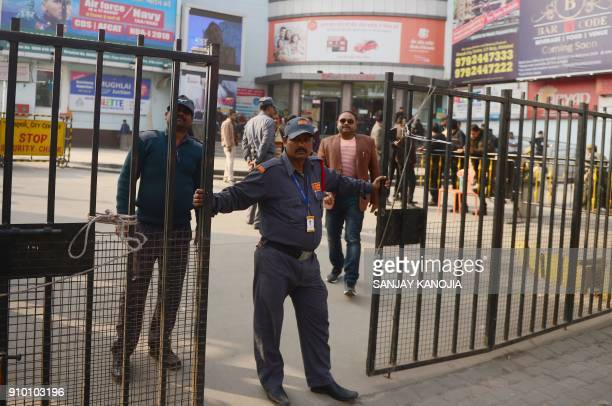 An Indian security guard stands outside a cinema which is not screening Bollywood film 'Padmaavat' due to threats of violence by Hindu hardliners in...