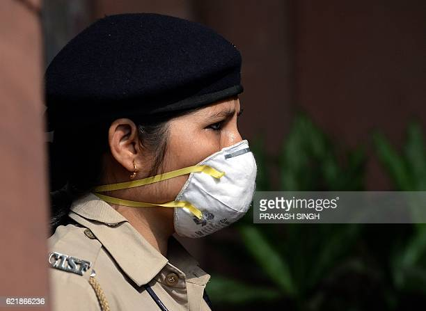 An Indian security official wears a mask while standing at the entrance to government offices in New Delhi on November 9 2016 Delhi has been shrouded...