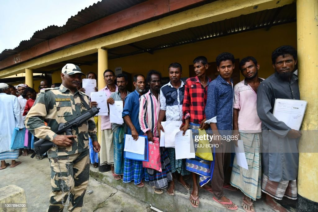 An Indian security personal stands guard as residents stand in a queue to check their names on the final list of National Register of Citizens (NRC) at a NRC Sewa Kendra (NSK) in Burgoan village in Morigoan district on July 30, 2018. - India on July 30 stripped four million people of citizenship in the northeastern state of Assam, under a draft list that has sparked fears of deportation of largely Bengali-speaking Muslims. Critics say it is the latest move by right-wing Prime Minister Narendra Modi to advance the rights of India's Hindu majority at the expense of its many minorities, in particular its over 170 million Muslims.