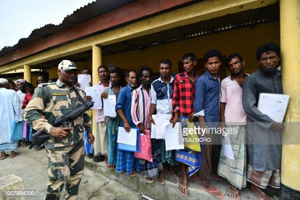 An Indian security personal stands guard as residents stand in a queue to check their names on the final list of National Register of Citizens at a...