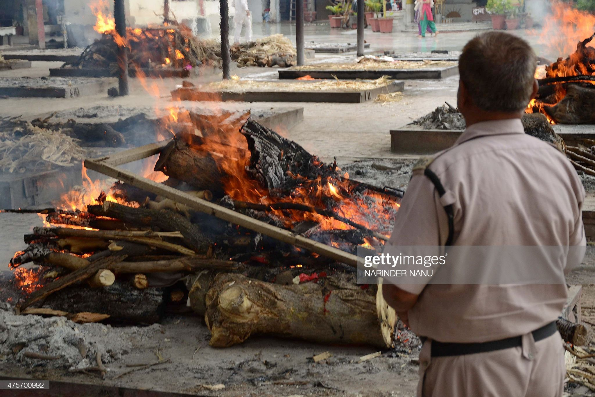 an-indian-security-personel-watches-the-cremation-of-an-unidentified-picture-id475700992
