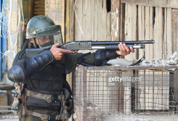 An Indian security personnel aims a pellet gun towards Kashmiri protestors during a clash between Indian government forces and Kashmiri villagers...