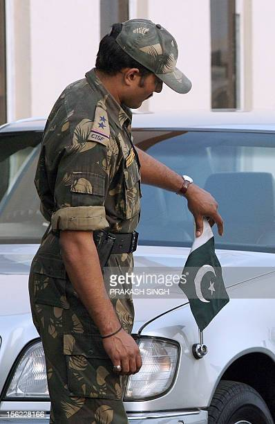 An Indian security personnel arranges Pakistan's national flag on the car of Pakistan's High Commissionner to India Aziz Ahmed Khan during the...