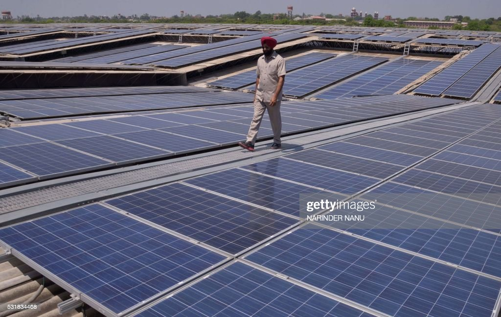 TOPSHOT An Indian security personnel poses for media as he walks over rooftops covered in solar panels at the Solar Photovoltaic Power Plant some...