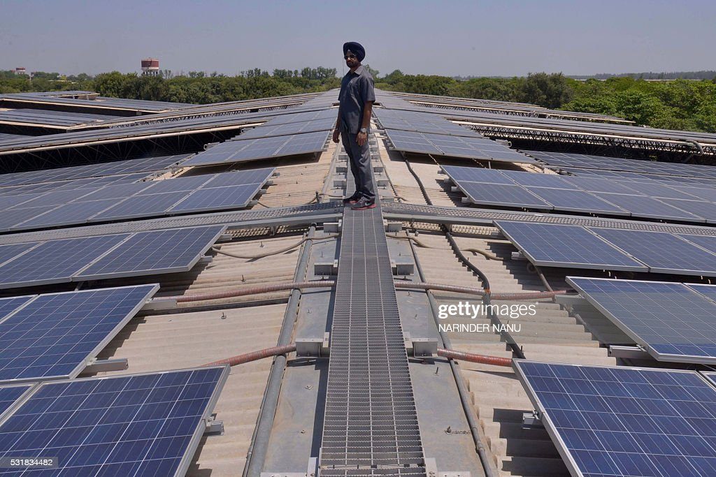 An Indian security personnel poses for media as he walks over rooftops covered in solar panels at the Solar Photovoltaic Power Plant some 45kms from..