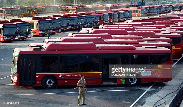 An Indian security personnel stands guard at the depot for Delhi Transport Corporation buses which will be used during the Commonwealth Games in New...