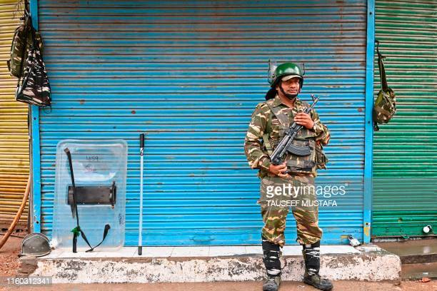 An Indian security personnel stands guard in front of closed shops during a curfew in Srinagar on August 8 as widespread restrictions on movement and...