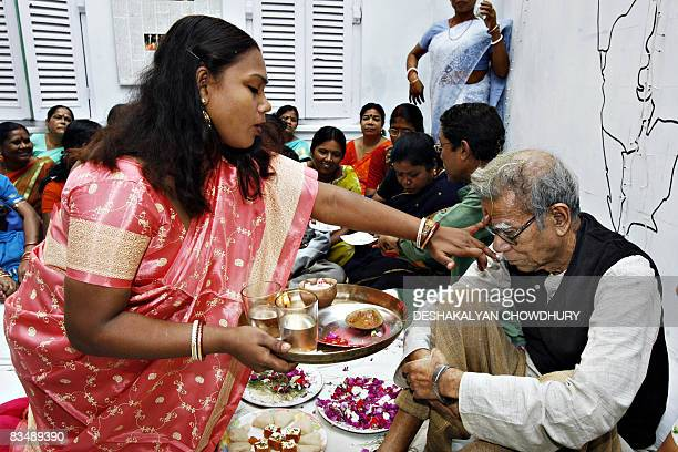 An Indian sex worker places a 'phonta' a religious holy mark of sandalwood paste on the forehead of Indian economist Amlan Datta in observance of...