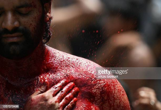 An Indian Shiite Muslim flagellates himself during the religious procession on the tenth day of the mourning period of Muharram which marks the day...