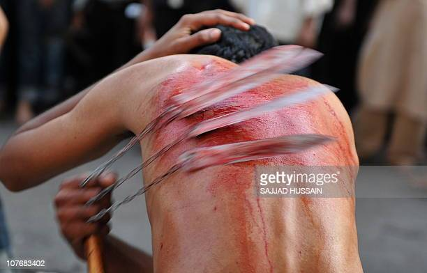 An Indian Shiite Muslim flagellates himself with a cluster of knives during a religious procession during the Ashura mourning period in Mumbai on...