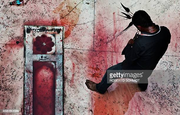 An Indian Shiite Muslim flagellates himself with knives over his head during Ashura commemorations in the courtyard of a local mosque in the old...