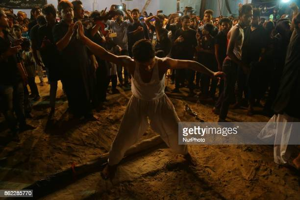 An Indian shiite muslim flagellates with blades to mark midnight Ashura procession in the old streets of Allahabad on October 172017 The mourning day...