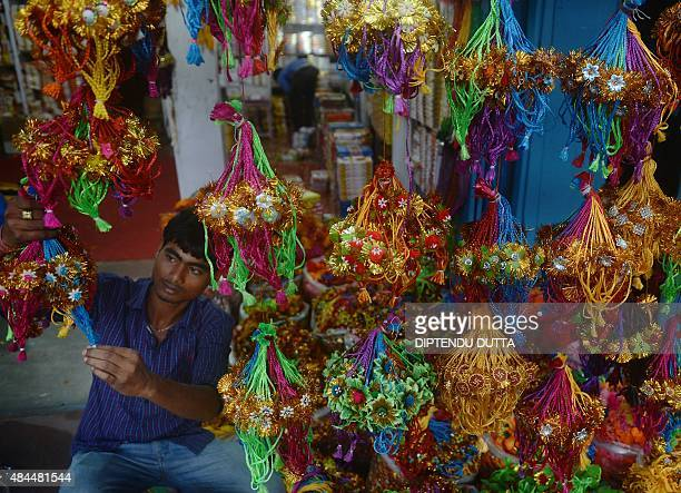 An Indian shop owner arranges at 'rakhi' at a roadside shop ahead of the Hindu festival Raksha Bandhan in Siliguri on August 19 2015 The annual...