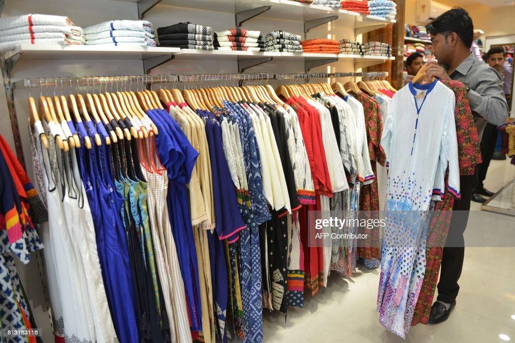 An Indian shop worker hangs shirts at a garment shop in Amritsar on July 12 2017 / AFP PHOTO / NARINDER NANU