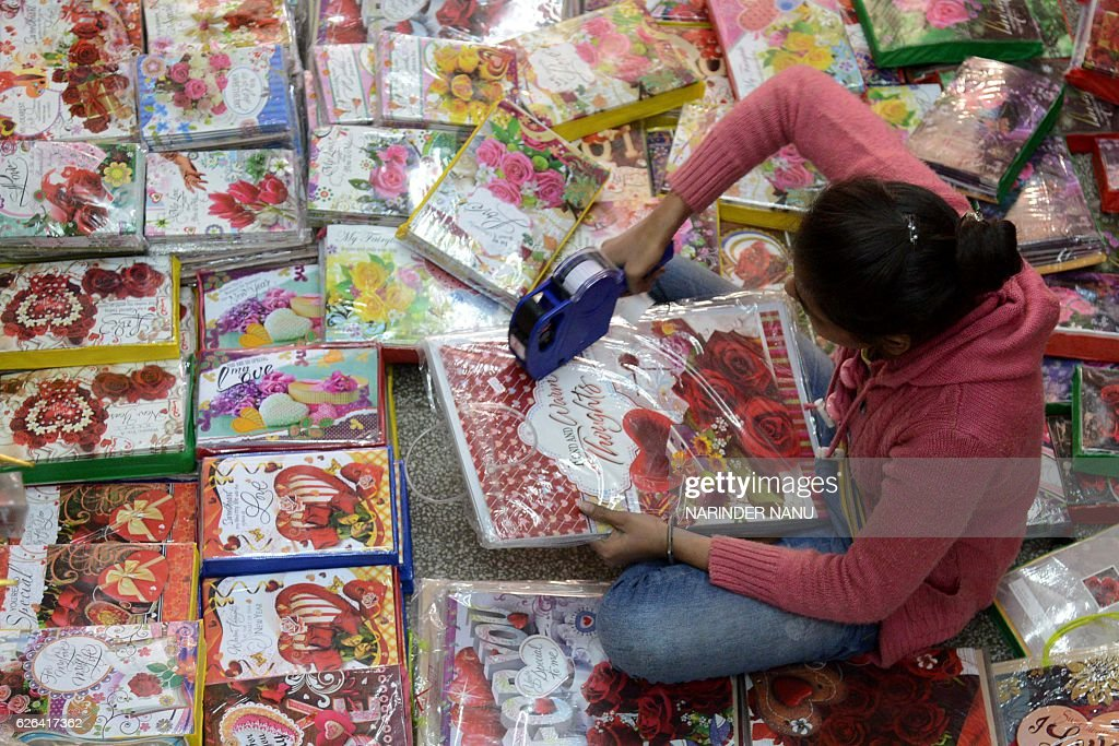 An Indian shop worker using labeling gun labeler to price greeting cards at a wholesale shop in Amritsar on November 29 2016 / AFP / NARINDER NANU