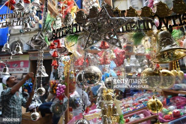 An Indian shopkeeper arranges Christmas decorations at an outdoor market in Mumbai on December 11 2017 / AFP PHOTO / INDRANIL MUKHERJEE