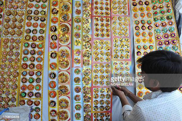 An Indian shopkeeper arranges rakhis at a stall in Hyderabad on August 11 ahead of the Raksha Bandhan festival which falls this August 13 The annual...