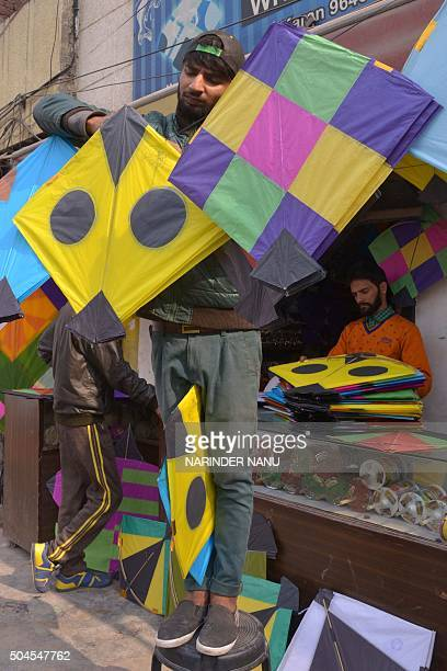 An Indian shopkeeper hangs kites for sale outside his shop in Amritsar on January 11 2016 The demand for kites is rising ahead of the Lohri harvest...