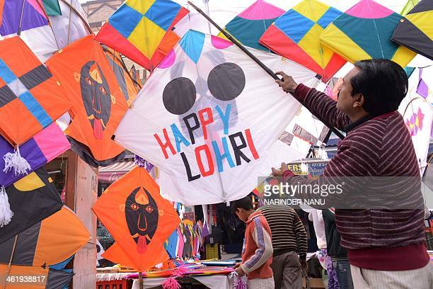An Indian shopkeeper hangs kites for sale outside his shop in Amritsar on January 12 2014 The demand for kites is rising on the eve of Lohri Festival...