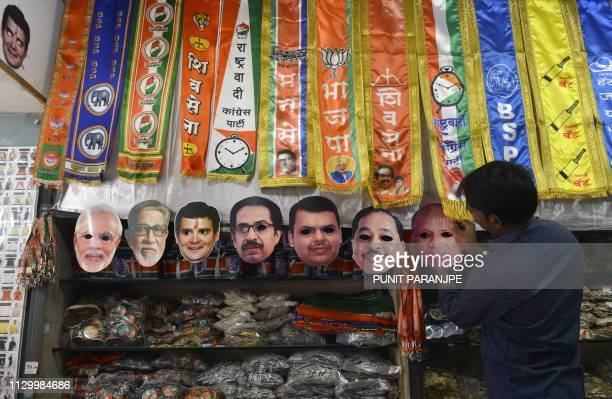 An Indian shopkeeper puts up face masks of political leaders at a shop in Mumbai on March 12 2019 India on March 10 announced a general election to...