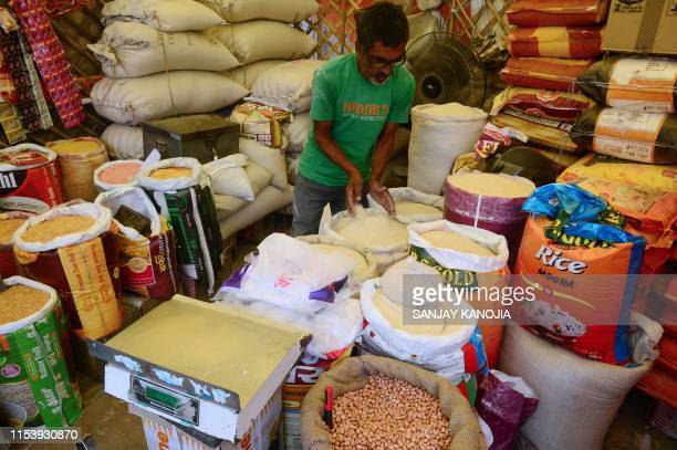 An Indian shopkeeper selling grains and legums waits for customers at a market in Allahabad on July 5 2019 India's newly reelected government...