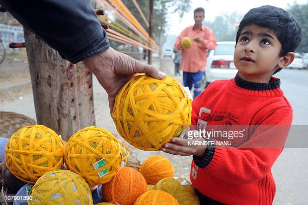 An Indian shopkeeper shows balls of coloured kite thread to a young boy by a roadside in Amritsar on January 5 2011 ahead of the Lohri Festival The...