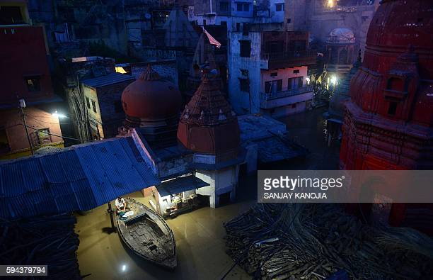An Indian shopkeeper sits on a boat outside his flooded shop at The Manikarnika Ghat in Varanasi on August 23, 2016. India's holy city of Varanasi...