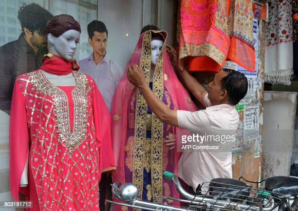 An Indian shopworker adjusts a dupatta at a clothing store in Amritsar on June 29 2017 India is bracing for its most significant reform in a...