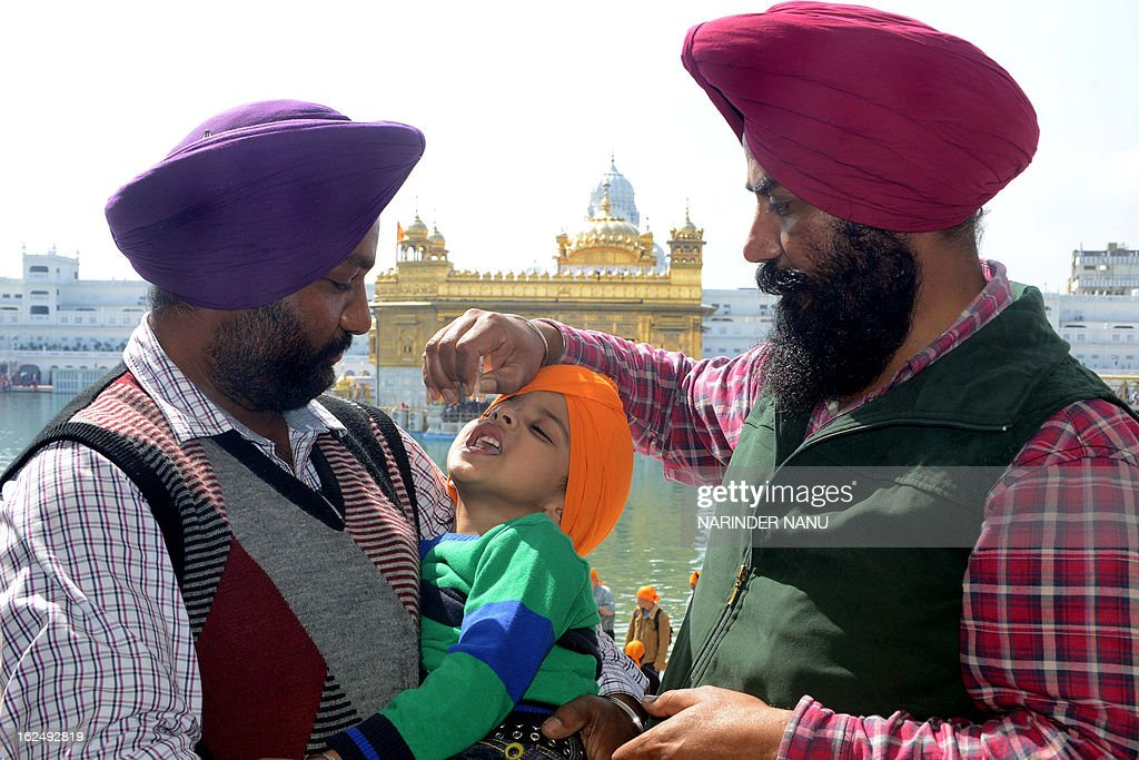 An Indian Sikh boy receives polio vaccination drops from a medical volunteer during an immunisation drive outside the Golden Temple in Amritsar on...