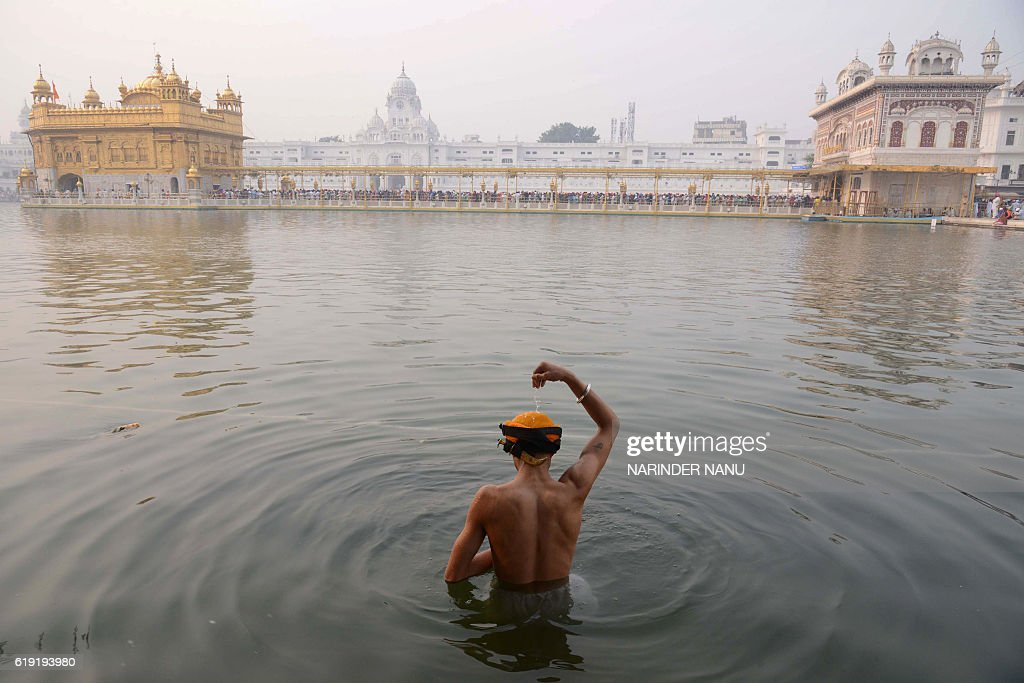 An Indian Sikh devotee bathes in the holy sarovar (water tank) on the occasion of Bandi Chhor Divas, or Diwali, at the Golden Temple in Amritsar on October 30, 2016. Sikhs celebrate Bandi Chhor Divas, or Diwali, to mark the return of the sixth Guru, Guru Hargobind Ji, who was freed from imprisonment and also managed to release 52 political prisoners at the same time from Gwalior fort held by Mughal Emperor Jahangir in 1619. / AFP / NARINDER