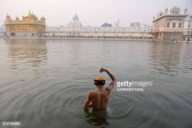 An Indian Sikh devotee bathes in the holy sarovar on the occasion of Bandi Chhor Divas or Diwali at the Golden Temple in Amritsar on October 30 2016...