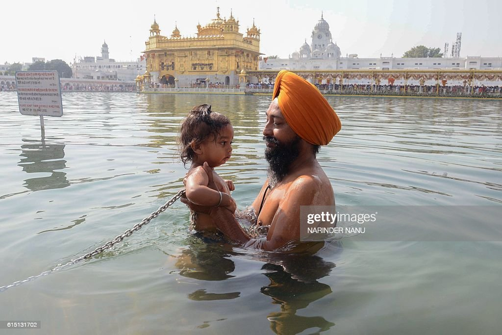 An Indian Sikh devotee bathes with his child in the holy sarovar at the Sikh Golden Temple shrine in Amritsar on October 17 2016 / AFP / NARINDER NANU