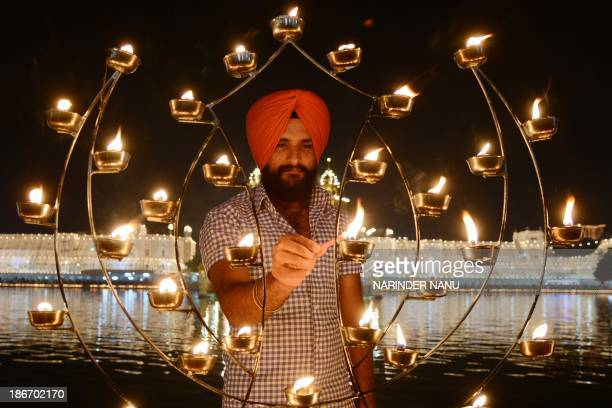 An Indian Sikh devotee lights candles at the illuminated Sikhism's holiest shrine Golden Temple in Amritsar on November 3 on the ocassion of Bandi...