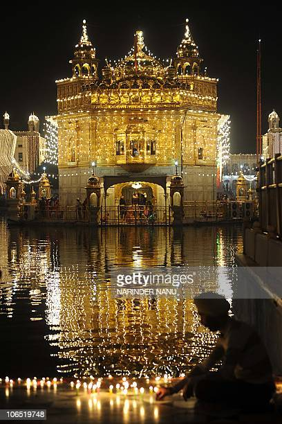 An Indian Sikh devotee lights candles in front of the illuminated Golden Temple in Amritsar on November 4 on the eve of the festival of Bandi Chhor...