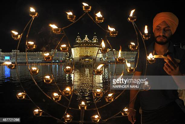 An Indian Sikh devotee lights candles on the occasion of Bandi Chhor Divas or Diwali at the illuminated Golden Temple in Amritsar India on October 23...