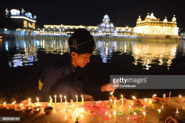 An Indian Sikh devotee lights candles to mark Bandi Chhor Divas or Diwali at the Golden Temple in Amritsar on October 19 2017 Sikhs celebrate Bandi...