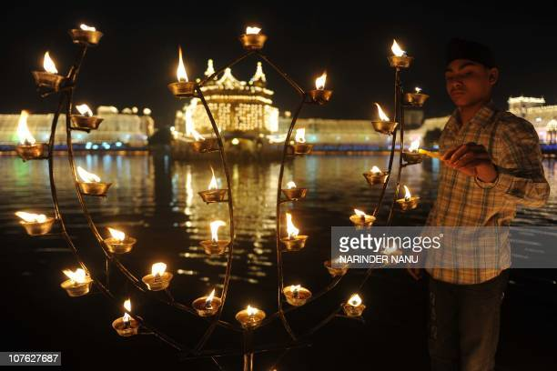 An Indian Sikh devotee lights lamps at the Golden Temple in Amritsar on November 5 on the occasion of Bandi Chhor Divas or Diwali Sikhs celebrate...