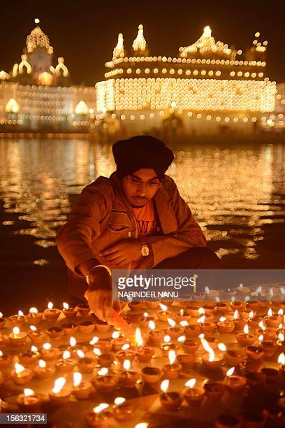 An Indian Sikh devotee lights oil lamps at the Golden Temple in Amritsar on November 13 on the ocassion of Bandi Chhor Divas or Diwali Sikhs...