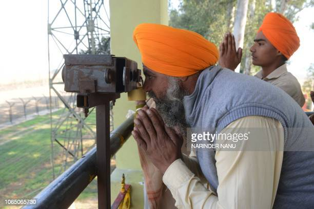 An Indian Sikh devotee offers prayers while looking through binocular towards the Gurdwara Kartarpur Sahib which is situated in Pakistan from Indian...