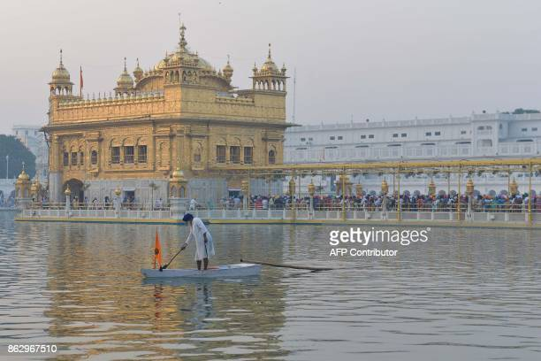An Indian Sikh devotee paddles in the holy water tank 'sarovar' during Diwali Festival at the illuminated Golden Temple in Amritsar on October 19...