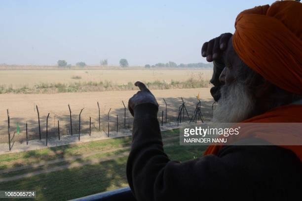 An Indian Sikh devotee points out towards the Gurdwara Kartarpur Sahib which is situated in Pakistan from Indian side at Dera Baba Nanak on the...
