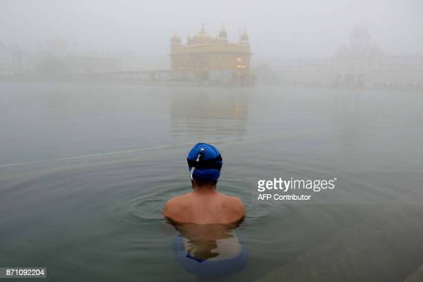 An Indian Sikh devotee takes a dip in the holy sarovar on a foggy day at the Golden Temple in Amritsar on November 7 2017 / AFP PHOTO / NARINDER NANU