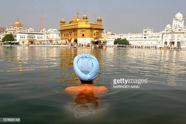 An Indian Sikh devotee takes a dip in the holy sarover at the Sikh Shrine Golden Temple in Amritsar on November 5 on the occasion of Bandi Chhor...