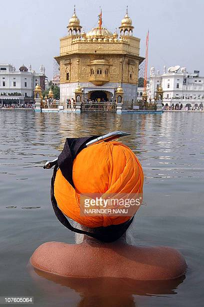 An Indian Sikh devotee takes a dip in the holy sarover of the Golden temple on the occasion of Bandi Chhor Divas in Amritsar 09 November 2007...